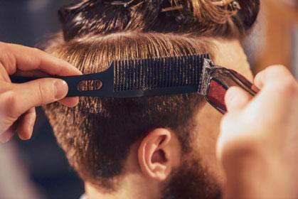 Foto von einem Herrenkopf von hinten während eines Haarschnittes